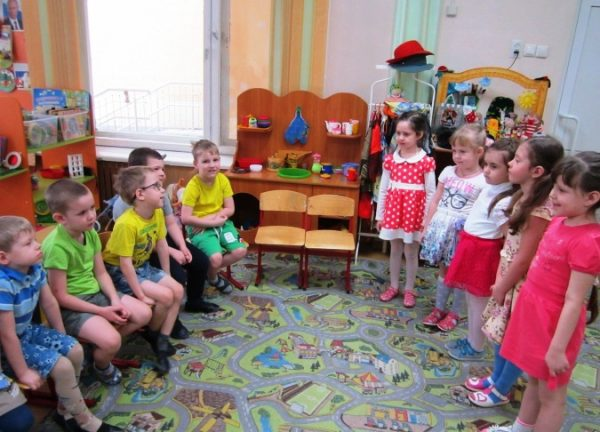 Мальчики сидят на стульях, девочки стоят напротив