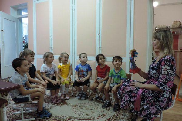 Педагог с куклой на руке рассказывает что-то сидящим полукругом детям