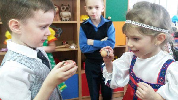 Мальчик и девочка играют с пасхальными яйцами