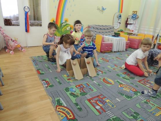 Дети катают крашеные яйца по жёлобу