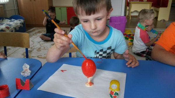 Мальчик раскрашивает пасхальное яйцо