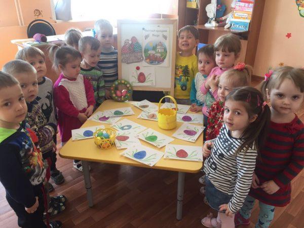 Дети стоят вокруг стола с рисунками крашеных яиц
