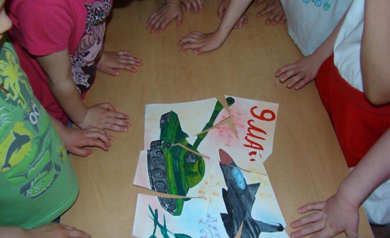 Дети стоят над пазлом-рисунком танка и самолёта