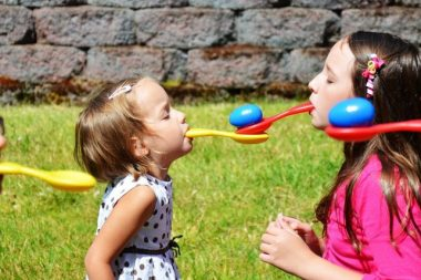 Девочки во рту держат ложки с яйцами