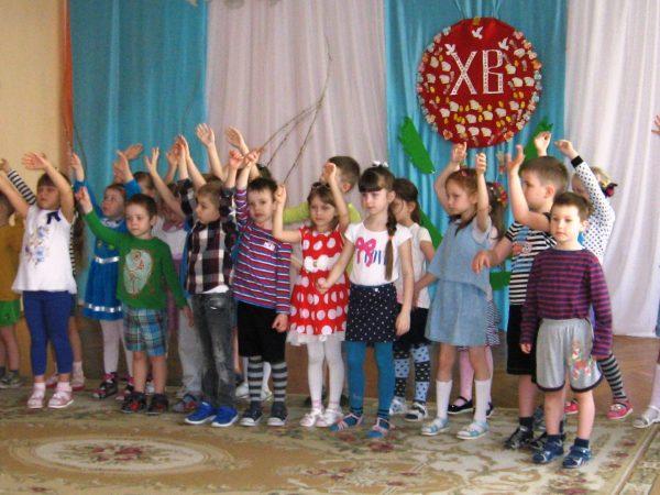 Дети стоят в зале с поднятой рукой