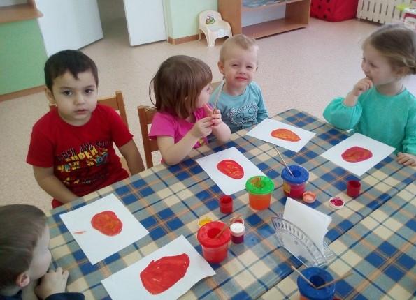 Дети сидят за столом, перед ними нарисованные яйца