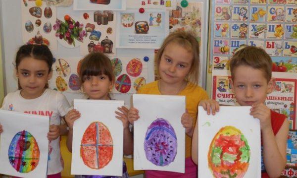 1Дети держат рисунки с изображением пасхального яйца
