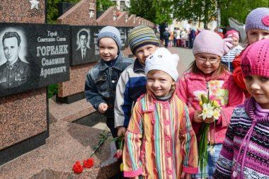 Дети стоят у мемориала героям СССР
