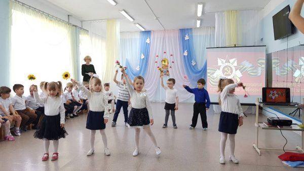 Дети танцуют с цветами на утреннике