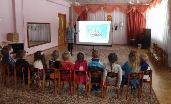 Педагог показывает детям военную технику на проекторе