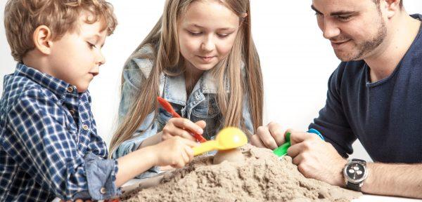 Папа и дети играют в кинетический песок