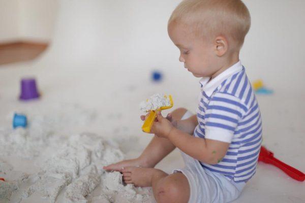 Малыш играет с кинетическим песком