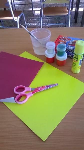 Картон жёлтого цвета, рядом гуашь, клей, ножницы, баночка с водой и кистью