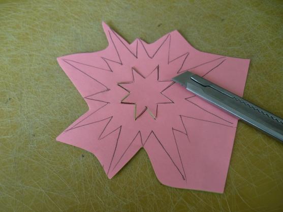 С помощью канцелярского ножа вырезается ажурная звёздочка