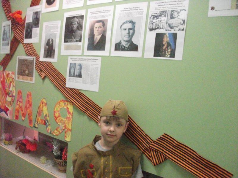 мальчик на фоне стенда ко Дню победы