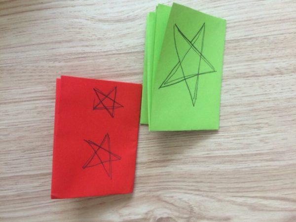 На сложенных листах красного и зелёного цветов нарисованы звёзды