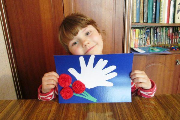 Девочка держит открытку с гвоздиками и голубем-ладошками