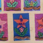 Выставка открыток со звездой, цветами и георгиевской лентой