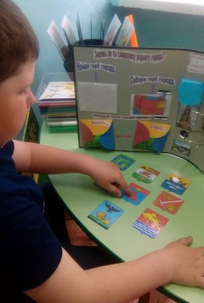 Мальчик смотрит на гербы городов и на один указывает пальцем