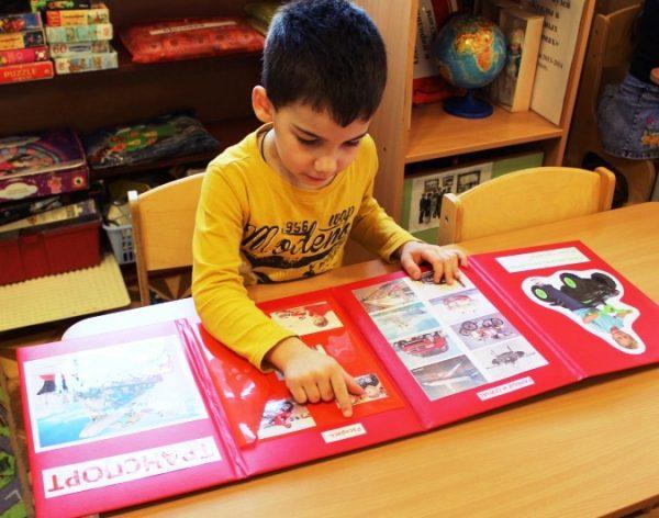 Мальчик занимается по лэпбуку красного цвета
