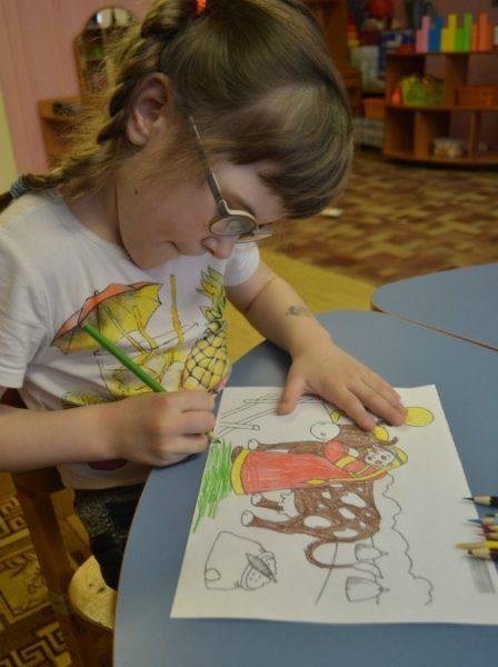 Девочка раскрашивает картинку