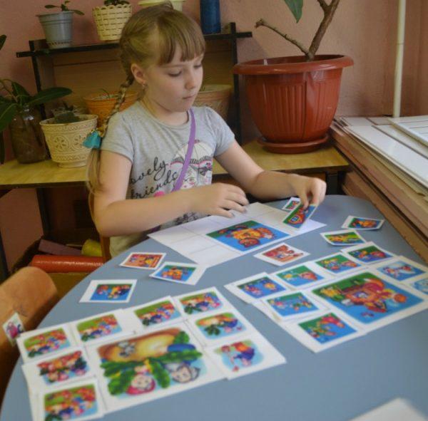 Девочка заполняет карточки лото