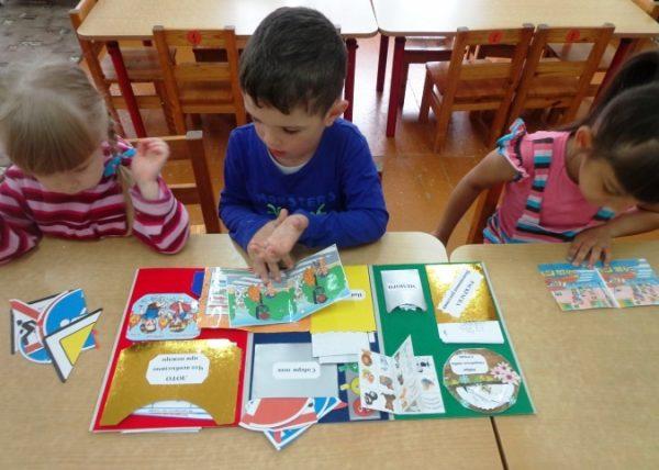 Мальчик и две девочки работают с лэпбуком