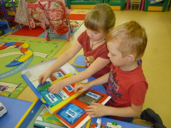 Мальчик и девочка работают с лэпбуком ПДД