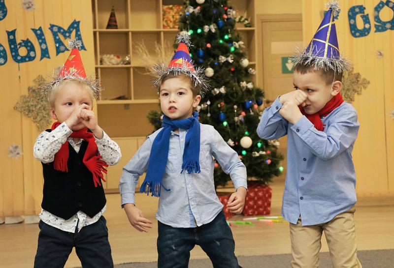 Три мальчика в колпачках и ёлка на заднем плане