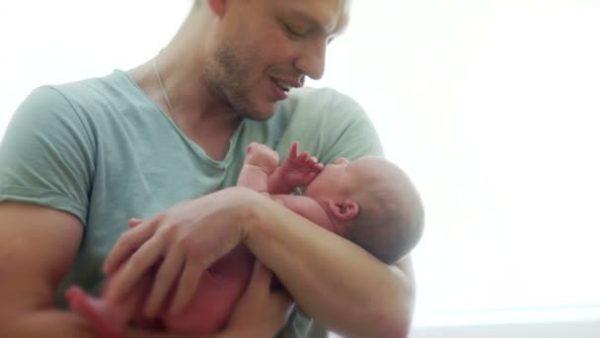 Мужчина держит на руках новорожденного