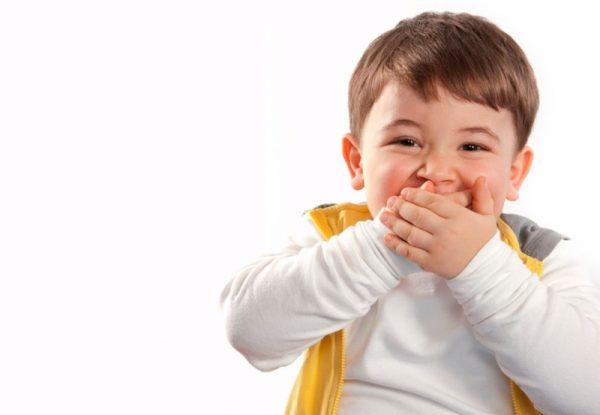 Мальчик прикрывает рот руками и смеётся