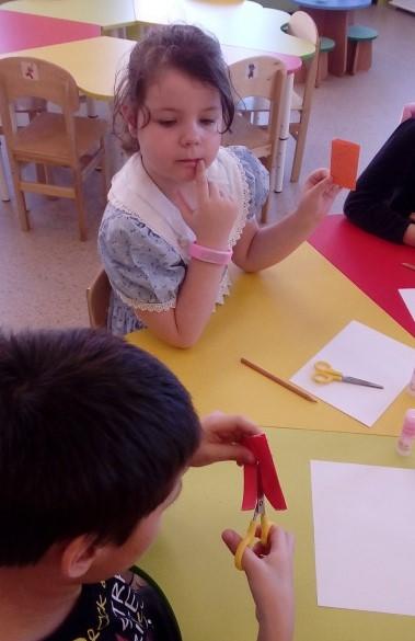 Мальчик вырезает половину человеческой фигуры, держа бумагу по линии сгиба