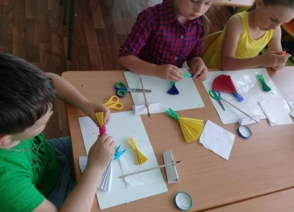 Дети фиксируют прищепкой маленькие гармошки (рукава)