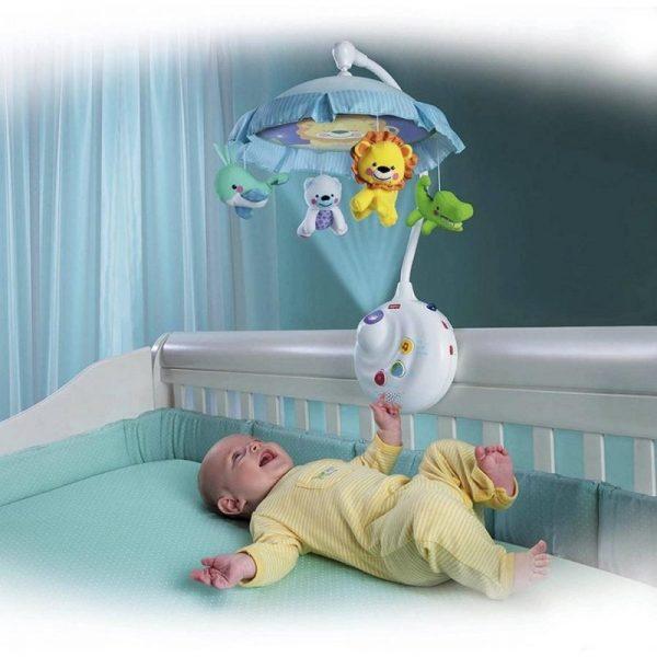 Младенец в кроватке смотрит на мобиль, трогает его и смеётся