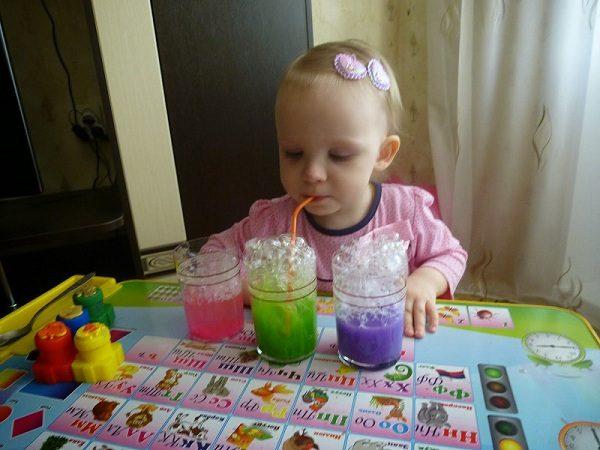 Маленькая девочка дует в стакан через соломинку