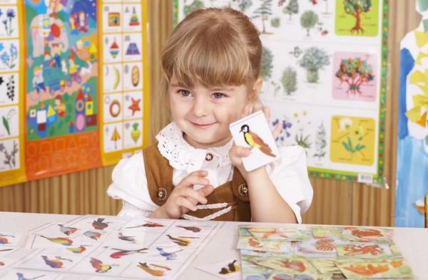 Девочка держит картинку с изображением птицы