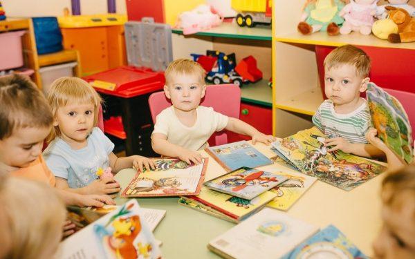 Малыши в детском саду сидят за столом с книжками