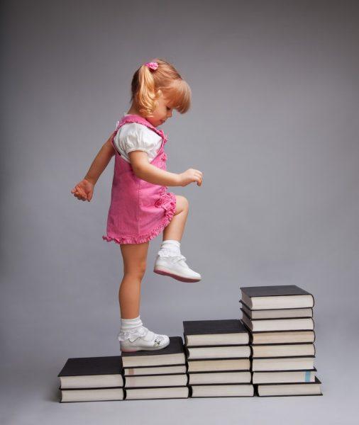 Девочка шагает по импровизированной лестнице из книг