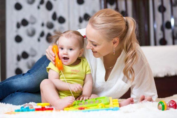 Девочка разговаривает по игрушечному телефону, который держит мама