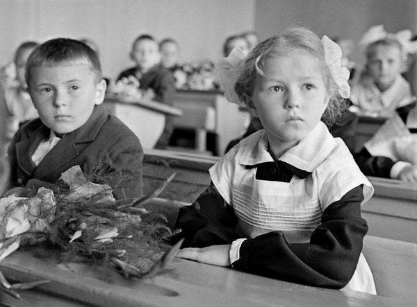 мальчик и девочка в белом фартуке за партой
