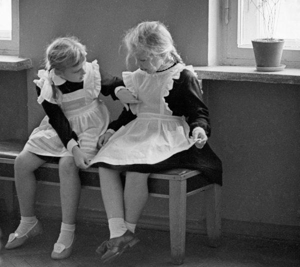 школьницы сравнивают свои белые фартуки