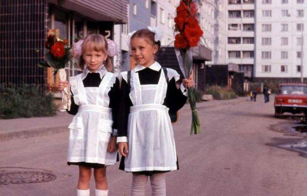 две девочки с букетами перед школой