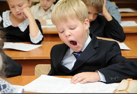 Мальчик зевает на уроке