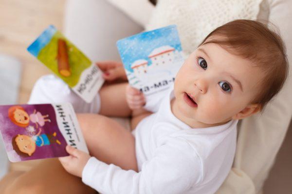 Ребёнок сидит на горшке и держит карточки с картинками и слогами
