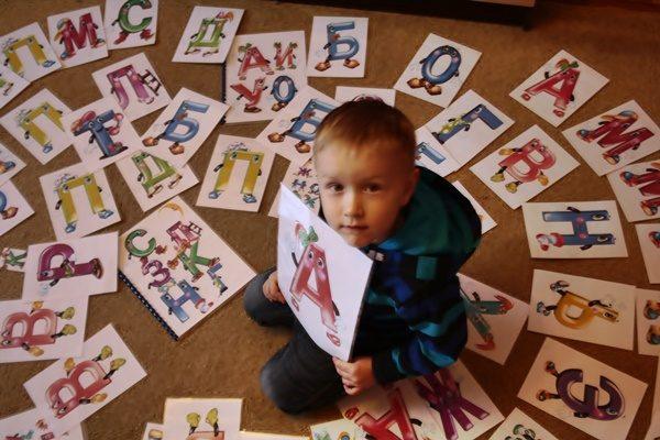 Мальчик, окружённый изображениями букв, в руках держит картинку с буквой А