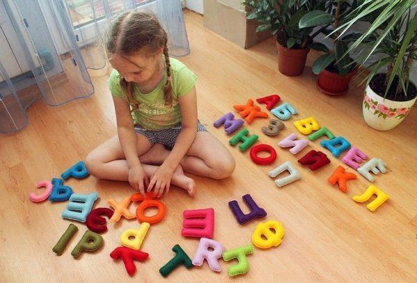 Девочка сидит на полу, рядом объёмные буквы из ткани