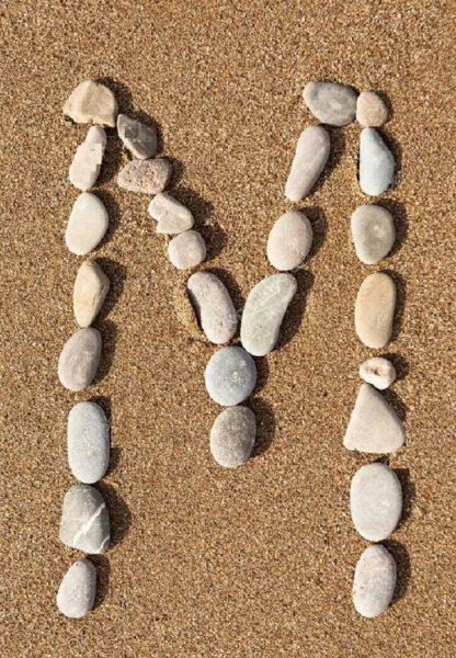 Буква М выложена из камешков