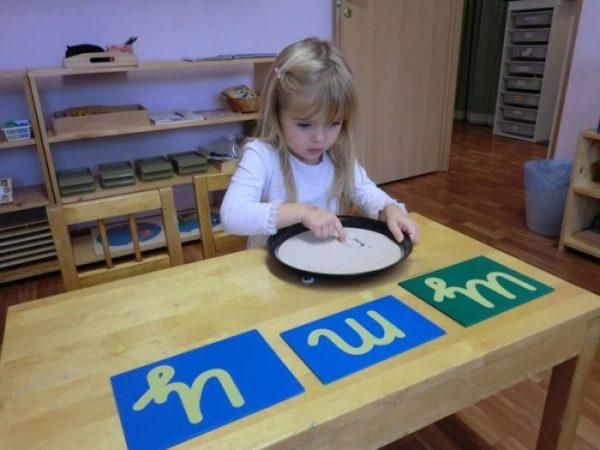 Девочка рисует буквы на песке, рядом на столе — шершавые буквы