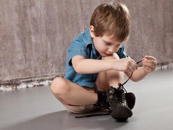мальчик сам завязывает шнурки на ботинках