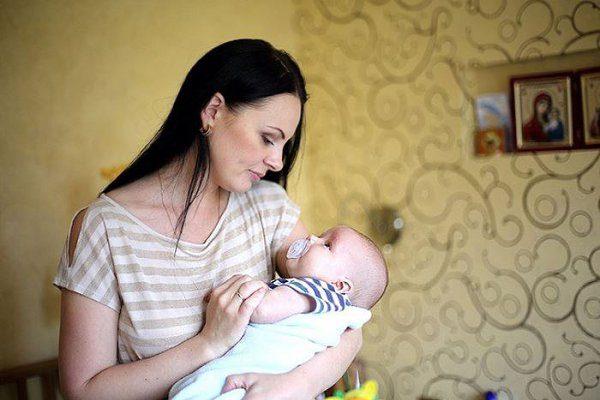 Мама укачивает младенца на руках